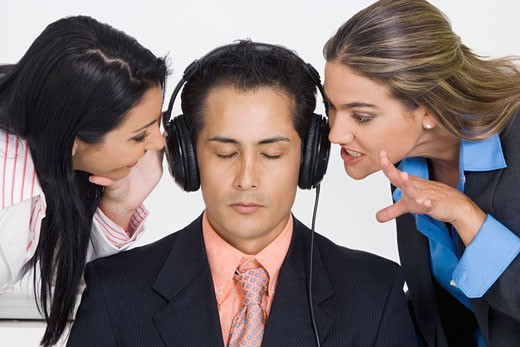 Close-up of a businessman listening to music while two businesswomen bothering him : Stock Photo