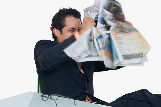 Businessman tearing a newspaper in frustration : Stock Photo