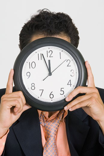 Stock Photo: 1663R-26365 Close-up of a businessman hiding his face with a clock