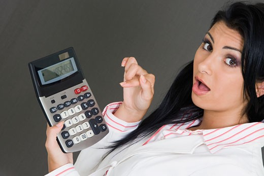 Portrait of a businesswoman holding a calculator and pointing at it : Stock Photo