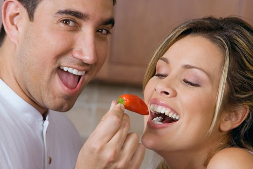 Stock Photo: 1663R-26394 Close-up of a mid adult man feeding a red chili pepper to a young woman