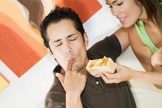 Young man licking his finger with a young woman holding a pastry : Stock Photo