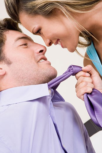 Stock Photo: 1663R-26422 Close-up of a young woman pulling a mid adult man towards her with his tie