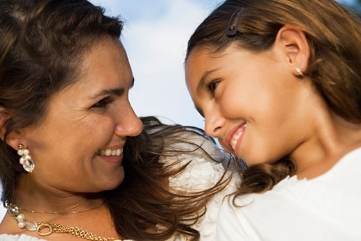 Close-up of a mid adult woman and her daughter looking at each other and smiling : Stock Photo