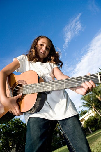 Stock Photo: 1663R-26512 Portrait of a girl playing a guitar