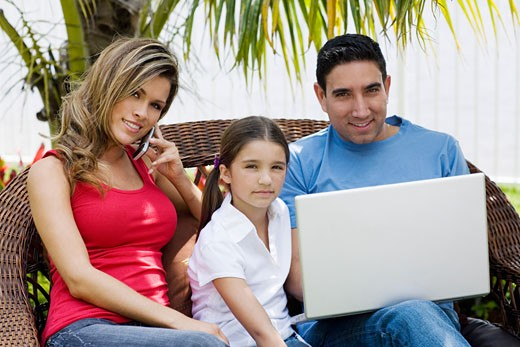 Portrait of a mid adult man using a laptop with a girl and a young woman sitting beside them : Stock Photo