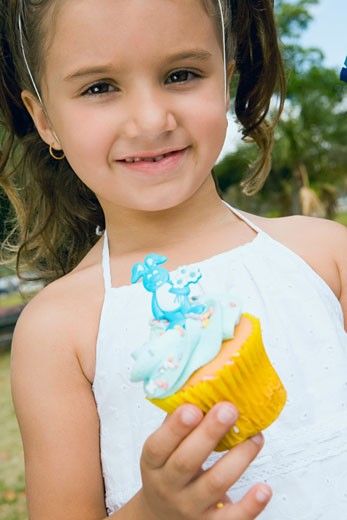 Portrait of a girl holding a cupcake and smiling : Stock Photo