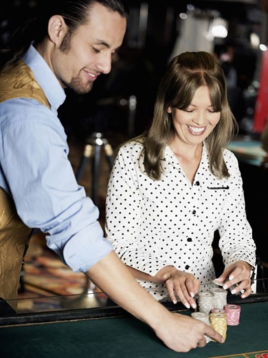 Casino worker arranging gambling chips on a gambling table with a young woman smiling beside him : Stock Photo