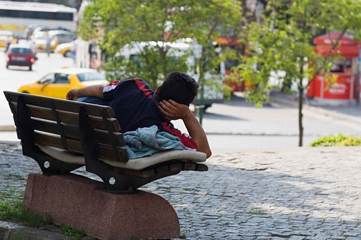Stock Photo: 1663R-30256 Rear view of a man lying on a park bench, Istanbul, Turkey