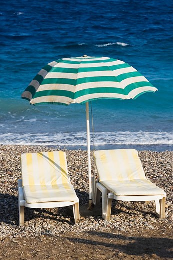 Two lounge chairs under a beach umbrella on the beach, Greece : Stock Photo