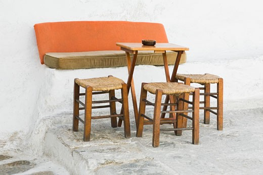 Stock Photo: 1663R-30397 Empty table with three stools in a restaurant, Mykonos, Cyclades Islands, Greece