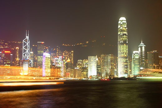 Skyscrapers lit up at night in a city, Victoria Harbor, Hong Kong Island, Hong Kong, China : Stock Photo
