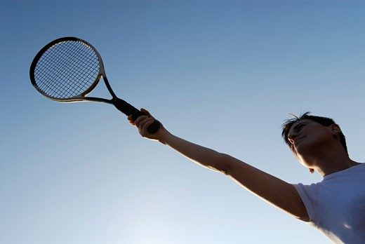 Low angle view of a mid adult woman holding a tennis racket : Stock Photo