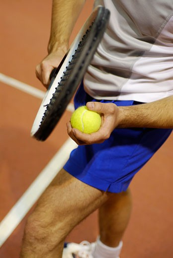 Stock Photo: 1663R-3148 Low section view of a man holding a tennis ball and a tennis racket