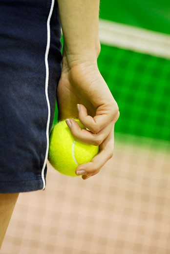 Mid section view of a Woman holding a tennis ball : Stock Photo