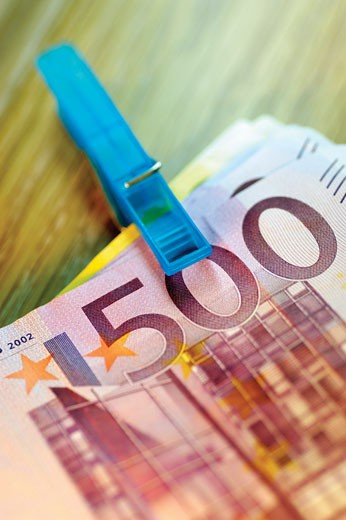 Close-up of a clothespin on a stack of assorted Euro banknotes : Stock Photo