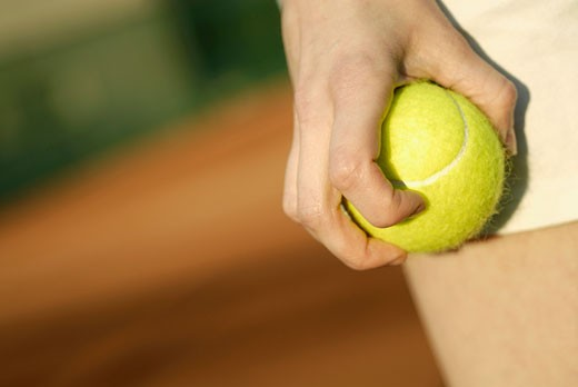 Close-up of a person's hand holding a tennis ball : Stock Photo