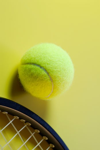 Close-up of a tennis ball with a tennis racket : Stock Photo