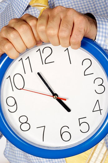 Mid section view of a businessman holding a clock : Stock Photo