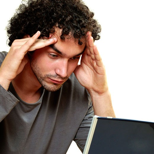 Stock Photo: 1663R-33577 Close-up of a young man in front of a laptop with his hands on his head