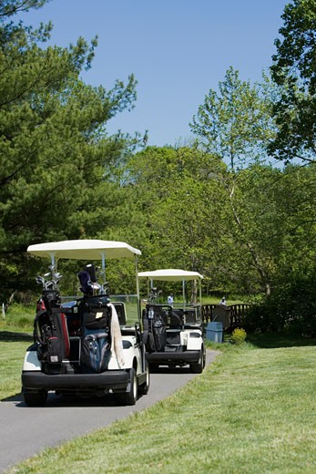 Two golf carts on a path : Stock Photo