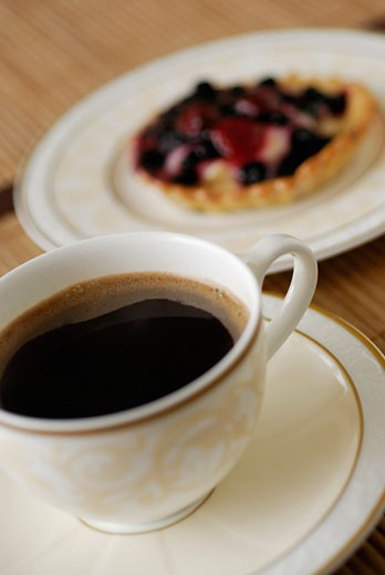 Close-up of a cup of black tea with a tart : Stock Photo