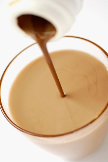 Chocolate milkshake pouring into a glass from a bottle : Stock Photo