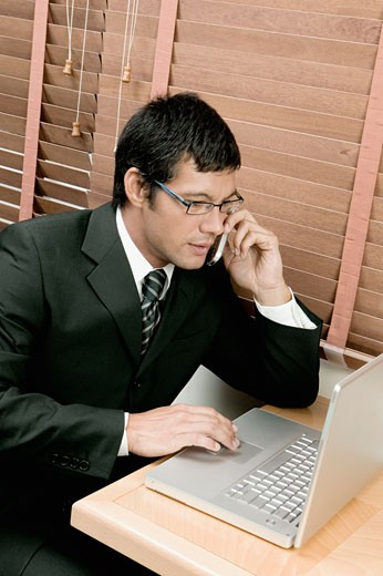High angle view of a businessman sitting in front of a laptop using a laptop and talking on a mobile phone : Stock Photo