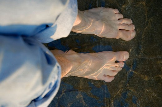 High angle view of a person ankles deep in water : Stock Photo