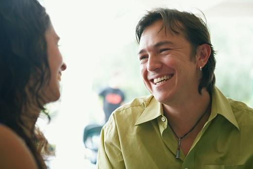 Close-up of a young woman and a mid adult man looking at each other and smiling in a restaurant : Stock Photo