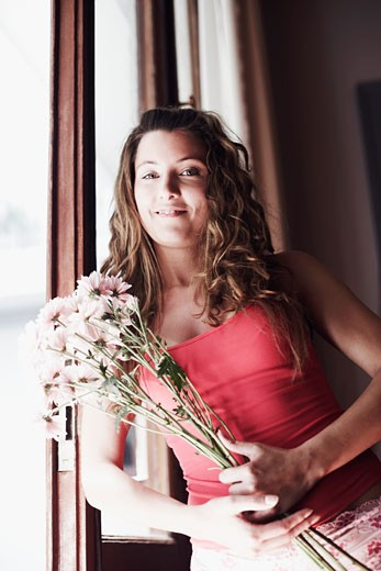 Portrait of a young woman holding a bunch of flowers : Stock Photo