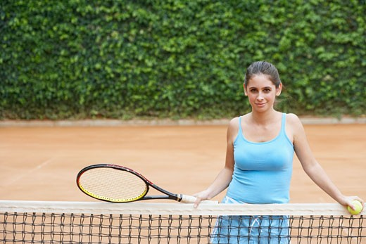 Stock Photo: 1663R-36275 Portrait of a young woman holding a tennis ball and a tennis racket