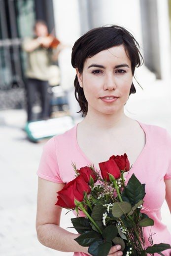 Portrait of a young woman holding a bunch of roses  : Stock Photo