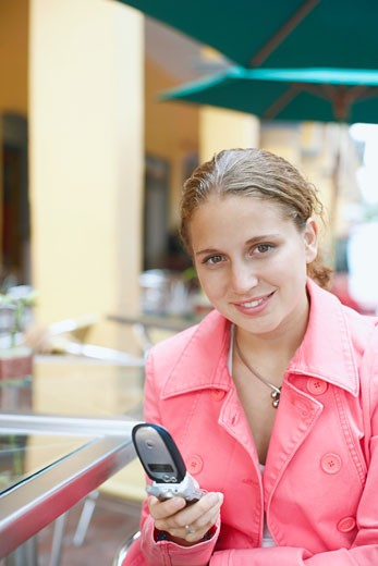 Stock Photo: 1663R-36996 Portrait of a young woman holding a mobile phone