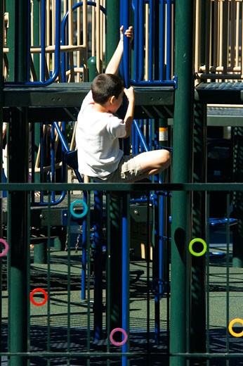 Rear view of a boy clambering on jungle gym : Stock Photo