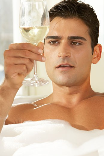 Close-up of a young man holding a glass of white wine in a bathtub : Stock Photo