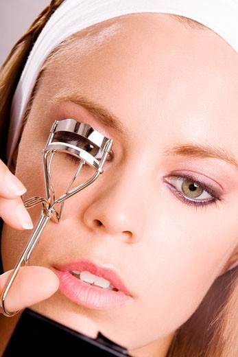 Stock Photo: 1663R-39609 Close-up of a young woman shaping her eyelashes with an eyelash curler