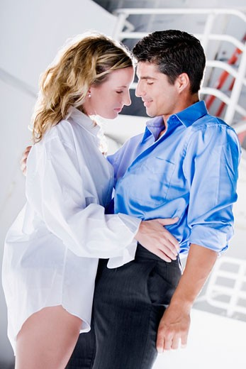 Side profile of a young woman and a mid adult man embracing each other : Stock Photo