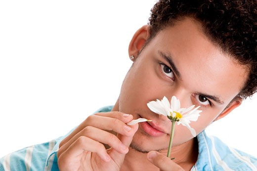 Portrait of a young man plucking petals of a flower : Stock Photo