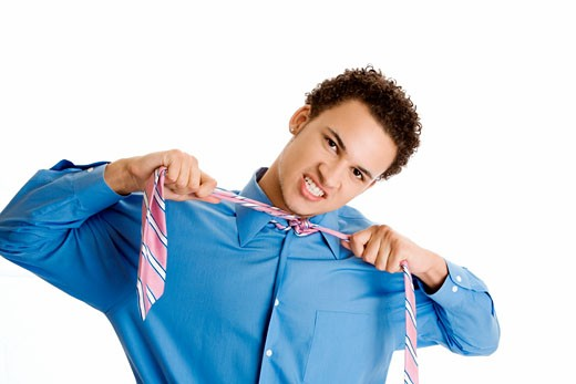 Stock Photo: 1663R-39875 Portrait of a young man pulling his tie