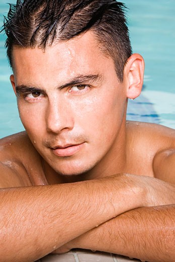 Portrait of a young man leaning at the edge of a swimming pool : Stock Photo