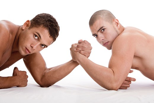 Portrait of two young men arm wrestling : Stock Photo
