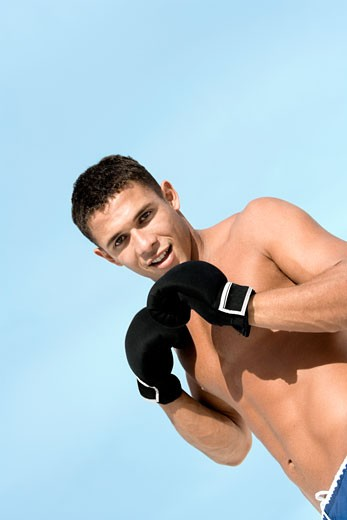 Stock Photo: 1663R-40846 Portrait of a young man wearing boxing gloves
