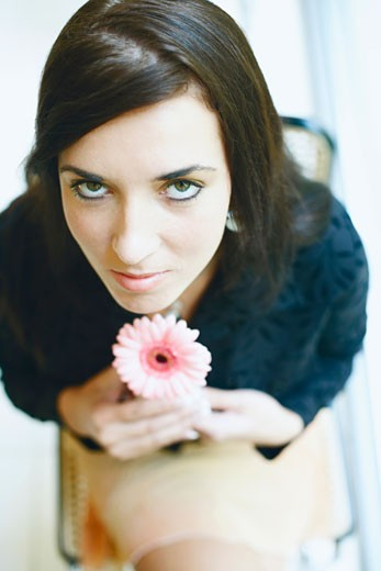 Portrait of a young woman sitting on a chair and holding a flower : Stock Photo