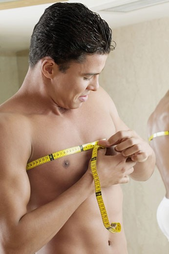 Close-up of a young man measuring his chest with a tape measure : Stock Photo