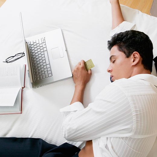 Stock Photo: 1663R-41494 High angle view of a businessman sleeping on the bed