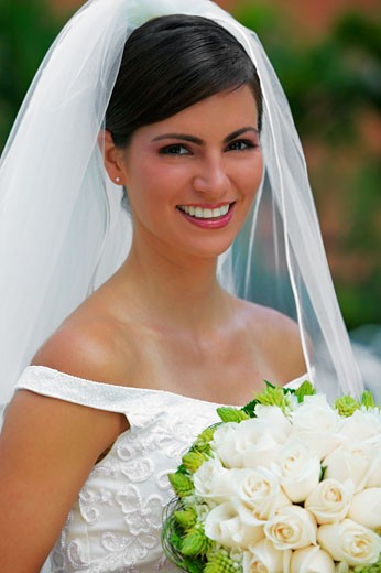 Portrait of a bride holding a bouquet of flowers and smiling : Stock Photo