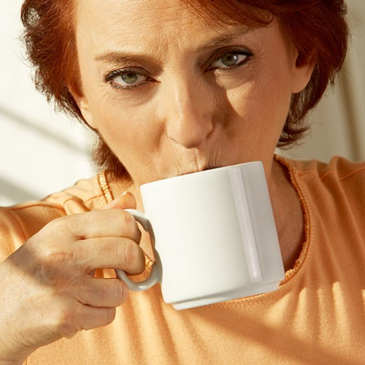Portrait of a senior woman drinking a cup of coffee : Stock Photo