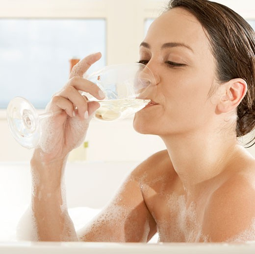 Close-up of a young woman drinking white wine in the bathtub : Stock Photo