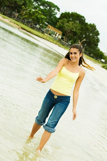 Stock Photo: 1663R-41838 Portrait of a girl wading in water on the beach